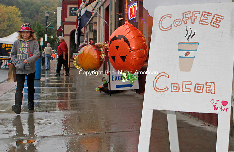 Winsted, CT-100414MK01 Kimberly McCarthy strolls in the pouring rain while inflatable jack-o-lanterns had a hard time keeping a smile during the annual Friends of Main Street fall foliage festival in Winsted on Saturday morning.  Friends of Main Street president, Fran Delaney said that over fifty vendors conceded to the weather at about noon time.  Delaney also said that this was the best participation from vendors in recent years unfortunately the precipitation kept shoppers and supporters away. Michael Kabelka / Republican-American