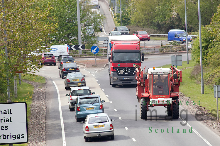 A75 road busy roundabout near Dumfries UK agricultural vehicle tractor with articulated lorry behind