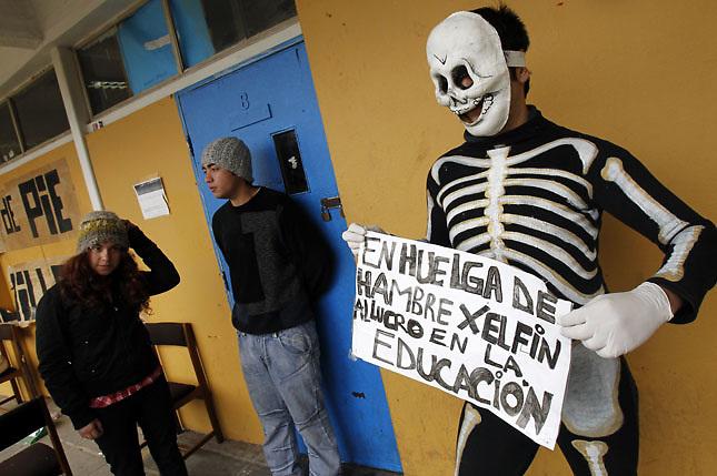 SCH10. BUIN (CHILE), 17/08/2011.- Estudiantes, uno de ellos disfrazado de esqueleto, custodian hoy, miércoles 17 de agosto de 2011, la entrada a un aula del liceo A131 de Buin (Chile) donde 5 estudiantes mantienen una huelga de hambre desde hace más de 30 días en demanda de una educación pública, gratuita y de calidad. EFE/Felipe Trueba