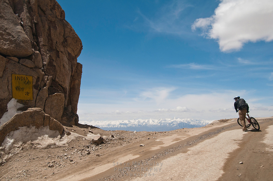 """Mountain biking past the """"India Gate"""" on the highest motorable road in the world,  Himalayan Mountains, Ladakh, India."""