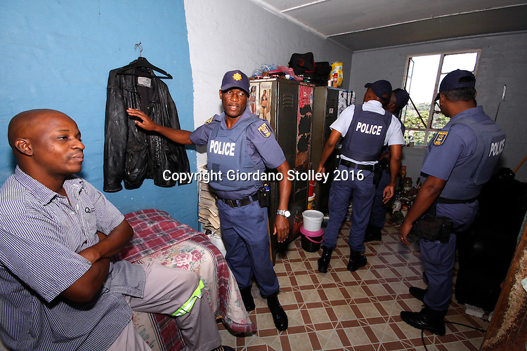 DURBAN - 13 May 2016 - Police officers search the room of a ressident (left,arms folded) at Durban's notorious Glebelands Hostels. They were looking for weapons, drugs and stolen goods. Hundreds of police officers from Durban, the KwaZulu-Natal south coast, Pretoria and the eThekwini Metro Police forces converged on the violent Glebelands Hostels on the edge of Durban's Umlazi township, which have seen numerous shootings that have leftt at least 61 people dead and scores injured. Picture: Allied Picture Press/APP
