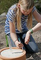 Kinder bauen eine Sonnenuhr, in einen mit Sand befüllten Blumentopf wurde eine Feder gesteckt, deren Schatten die Uhrzeit zeigen soll, nun wird die aktuelle Uhrzeit am Rand aufgetragen an der Stelle, auf die der Schatten der Feder zeigt