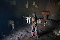 BAKO, ETHIOPIA - NOVEMBER 12: The son of Nodajo Gobena, a farmer who was pushed out from his land when the government sold a leases to Indian farmers in the area, carries some maize in one of the family houses on November 12, 2010 in Bako, Ethiopia. Photo by: (Per-Anders Pettersson)