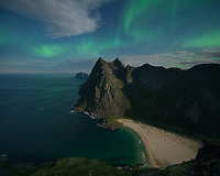 Northern lights shine in sky over Horseid beach, Moskenesøy, Lofoten Islands, Norway