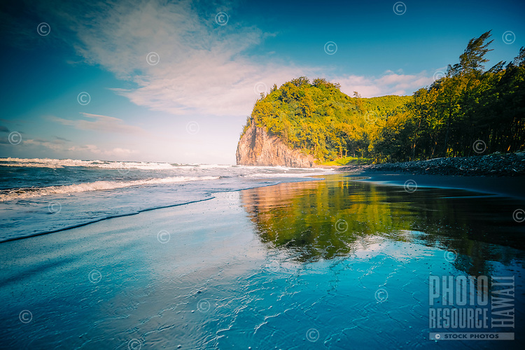 A hiker's view of the black sand of Pololu Beach on the North Kohala coastline of the Big Island.