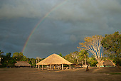 Aldeia Baú, Para State, Brazil. The village with a rainbow in the golden afternoon sunlight; the men's hut in the centre of the village.