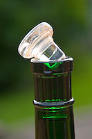 Alternative closure to replace natural cork: a glass stopper with a sealing silicone ring and a metallic cover cap. Series showing how to open it with the thumb of one hand. Bottle of Schloss Vollrads white German wine. Called Vino-Lok and produced by Alcoa.