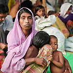 A Rohingya woman, having just crossed the border from Myanmar, comforts her children as she waits to complete registration in the Kutupalong Refugee Camp near Cox's Bazar, Bangladesh. More than 600,000 Rohingya refugees have fled government-sanctioned violence in Myanmar for safety in this and other camps in Bangladesh.