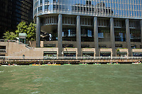 A raft of kayakers pass under the Trump International Hotel and Tower on the Chicago River.