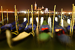 The night view of gondolas in a blurred motion with San Giorgio Maggiore church in the background. Venice. Italy