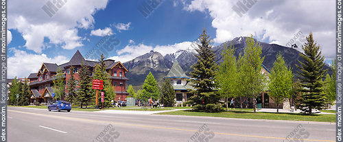 Panoramic springtime street scenery of Canmore, town in Bow valley of Alberta's Rockies with mountains in the background. Canmore, Alberta, Canada. 2017