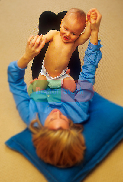 young mother laying on floor playing with toddler on her lap