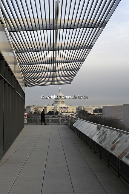 A visitor stands on the terrace of the Newseum on Pennsylvania Avenue as the capitol is decorated with flags for Barack Obama's inauguration day on Washington, DC on January 14, 2008.