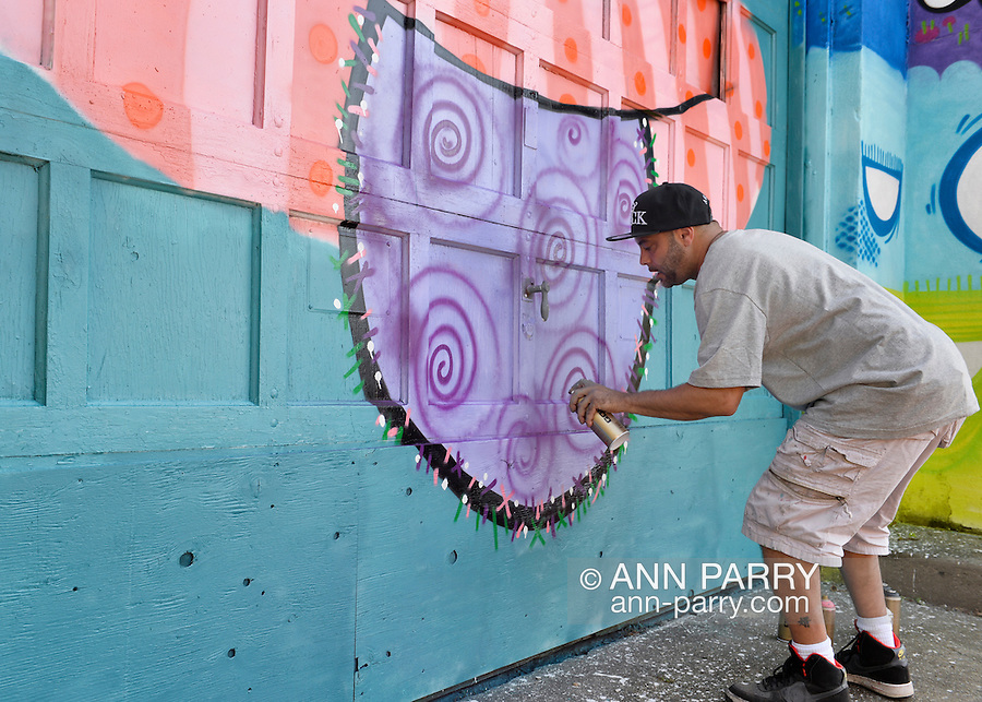 """Huntington, New York, U.S. 24th August 2013. PHETUS, world famous graphic designer for hip hop artists, and former graffiti artist from Huntington, is painting on the back of the Huntington Arts Council building, during the the art event """"Off the Walls"""" Block Party, by SPARKBOOM, a project the council created to help emerging artists, showcase talents, and help its artistic family network."""