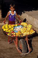 small smiling mexican boy with a whellbarrow ful of fruits for sale. Sweet
