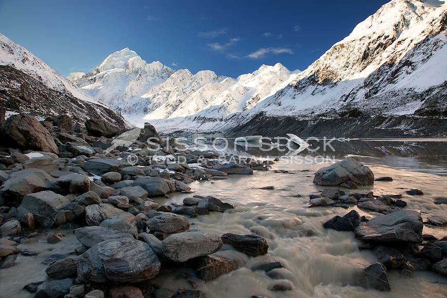 Glacial water flows out of Hooker Lake with Mount Cook seen in the background