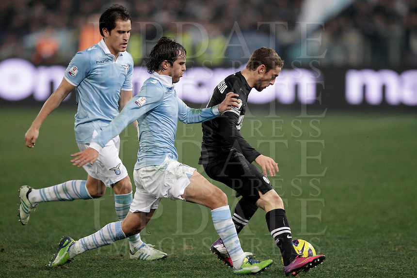 Calcio, semifinale di ritorno di Coppa Italia: Lazio vs Juventus. Roma, stadio Olimpico, 29 gennaio 2013..Juventus midfielder Claudio Marchisio, right, is challenged by Lazio midfielders Alvaro Gonzalez, of Uruguay, center, and Cristian Ledesma, during the Italy Cup football semifinal return leg match between Lazio and Juventus at Rome's Olympic stadium, 29 January 2013..UPDATE IMAGES PRESS/Riccardo De Luca