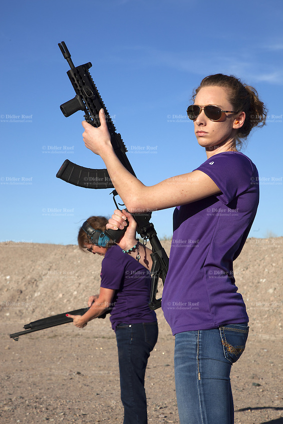 """USA. Arizona state. Peoria. Peoria is distant 50 km from Phoenix. Cowtown Shooting Range. Cowtown is a semi-private outdoor shooting range and firearms training facility. Carrie Lightfoot (L) holds a Beretta 1301 Tactical Semi-Auto 12-Gauge Shotgun while her colleague Ashley Suris an AK-47. Both women train their shooting skills with two semi-automatic rifles. Carrie Lightfoot is the founder and CEO of """"The Well Armed Woman. Where the Feminine and Firearms Meet"""" which sell online resources for women gun owners. The Beretta 1301 Tactical is a gas operated semi-automatic shotgun designed for law enforcement and home defense. The AK-47 (also known as the Kalashnikov, AK, or Kalash) is a selective-fire automatic or semi-automatic gas-operated 7.62×39mm assault rifle, developed in the Soviet Union by Mikhail Kalashnikov. A firearm is a portable gun, being a barreled weapon that launches one or more projectiles often driven by the action of an explosive force. Most modern firearms have rifled barrels to impart spin to the projectile for improved flight stability. The word firearms usually is used in a sense restricted to small arms (weapons that can be carried by a single person). The right to keep and bear arms is a fundamental right protected in the United States by the Second Amendment of the Bill of Rights in the Constitution of the United States of America and in the state constitutions of Arizona and 43 other states. 28.01.16 © 2016 Didier Ruef"""