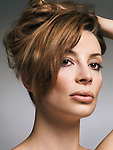 Beauty portrait of a woman with light brown hair in updo and natural makeup in her early thirties isolated on gray background Image © MaximImages, License at https://www.maximimages.com