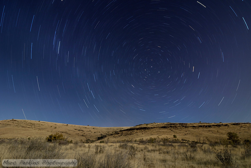 "A long-exposure image of the moonlit hills above Prescott Valley, Arizona.  This is a single-frame ~30-minute capture.  Due to the long exposure the planet's rotation on its axis causes the stars to leave trails (""star trails""), with the stars further from the north star having longer trails."
