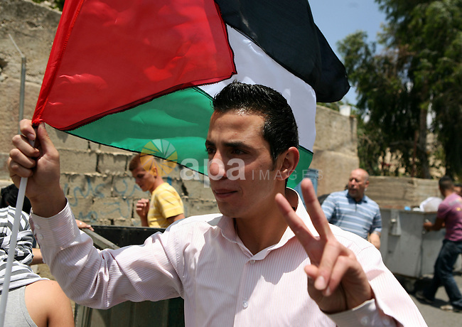 A Palestinian youth waves his national flag during clashes in the West  Bank village of Nabi Saleh, on 28 May 2010. Palestinians protest weekly against the neighbouring Jewish settlement of Halamish. photo by Eyad Jadallah