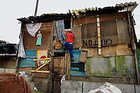A Colombian man climbs a wooden shack in the 'Invasión', a temporary slum in Bogota, Colombia, 1 April 2006. The internal armed conflict in Colombia together with lack of social network caused appearence of small invasion slums in all Colombian urban zones in last years. These illegal settlements rise quickly in free uncontrolled spaces between industrial buildings, both in the city centres and peripheries. Shacks do not have sanitation network, neither electricity. Most of their inhabitants are war fugitives violently displaced from their original lands in the country by guerrilla or paramilitary forces. Picking up the rubbish and recycling it is a common survive strategy for people living in these temporal ghettos until those are not dismantled by city administration.