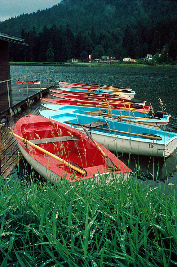 Colorful, abandoned row boats at dock after the rain on a storm- darkened lake. boat. Seefeld Tyrol Austria.