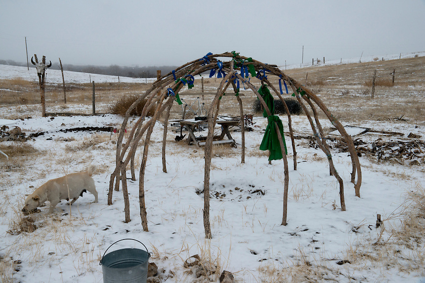 A structure of a sweat lodge next to the trailer of Cornel Conway. A Vietnam veteran, Cornel used in the past traditional healing methods to cure his PTSD. As many others he continue practicing this tradition. After an uprising in 1973at the town of Wounded Knee and its violent repression by federal authorities sparked a renewal of the Lakota culture: a culture which had been suppressed for most of the 20th century.Religious ceremonies, Sundances and sweats that had been maintained in secret are practiced in public again.