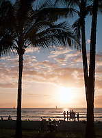 People watch the sunset over Waikiki Beach at Honolulu, O'Ahu, Hawai?i