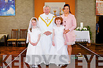 COMMUNION DAY: The puplis of Ballincrossig NS at their First Holy Communion at St Peter and St Paul Church, Ballyduff on Saturday l-r: Aoibhe Reilly, Fr Brendan Walsh, Katie Mahoney and Ms Elaine Scanlon.