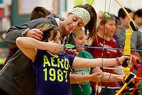NWA Media/DAVID GOTTSCHALK - 12/17/14 - Cheyanne (cq) Plunkett, physical education teacher at Asbell Elementary School in Fayetteville, reaches in to hold back the bangs of fifth grade student Autumn Sheppard during class Wednesday December 17, 2014. This is the first year for archery at the school in the class's of Plunkett and teacher Trey Selmon and stresses safety, accuracy and hand eye coordination.