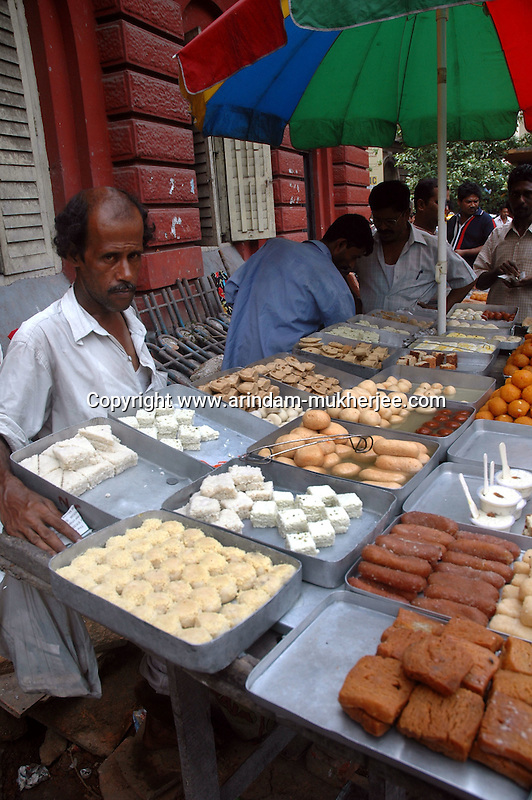 An Indina man selling sweets at a footpath in  Dalhousie area of Kolkata. Street food stalls are serving the office goers for decades. All kind of Indian foods are available on the street at an affordable price. They sale them openly. Street food stalls are another results of unempoloyment and over poppulation. They serve millions of people in India. Kolkata, West Bengal,  India  7/18/2007.  Arindam Mukherjee/Landov