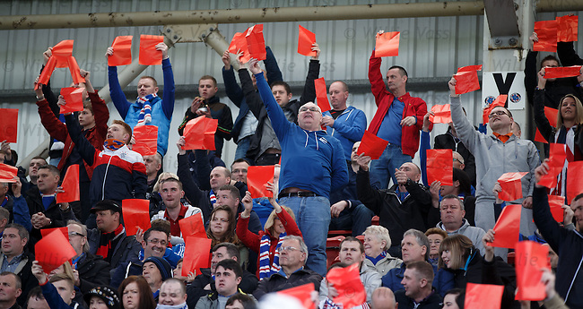 Rangers fans hold up red cards in protest at the board