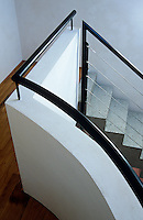 A simple concrete staircase is enhanced by a black balustrade