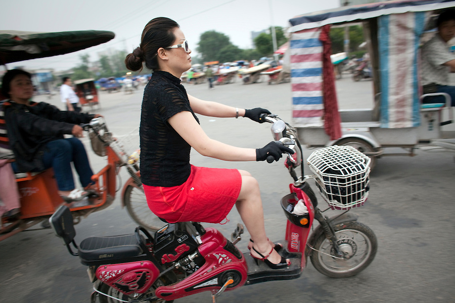 A stylish woman in a red skirt, gloves and heels zips past on an electric bicycle in Bozhou.