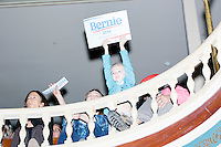 Julianna Holmes, 5, of Somersworth, New Hampshire, holds a Sanders campaign sign in the balcony while Vermont senator and Democratic presidential candidate Bernie Sanders speaks at a town hall at the Rochester Opera House in Rochester, New Hampshire, on Thurs., Feb. 4, 2016. Press and attendee turnout was low for the event because of scheduling issues. The rally had been scheduled for the previous day, postponed, and then rescheduled just a few hours before the event took place. Later that night, Sanders took part in an MSNBC-sponsored debate with Hillary Rodham Clinton.