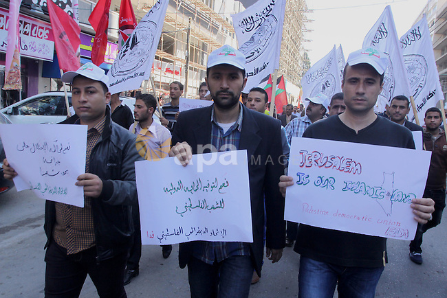 Members of the Palestinian factions hold banners and national flags during a demonstration to show solidarity with Jerusalem and against the recent visits by Jewish activists to al-Aqsa mosque, in Gaza city November 9, 2014. In recent weeks there have been near-daily clashes between the stone-throwing Palestinians and Israeli riot police in occupied East Jerusalem. Some of the attacks have turned deadly. The unrest was triggered by Muslim fears of Jewish encroachment at the sacred site, a hilltop plateau known to Muslims as Haram as-Sharif, or Noble Sanctuary, and to Jews as the Temple Mount. Photo by Mohammed Asad