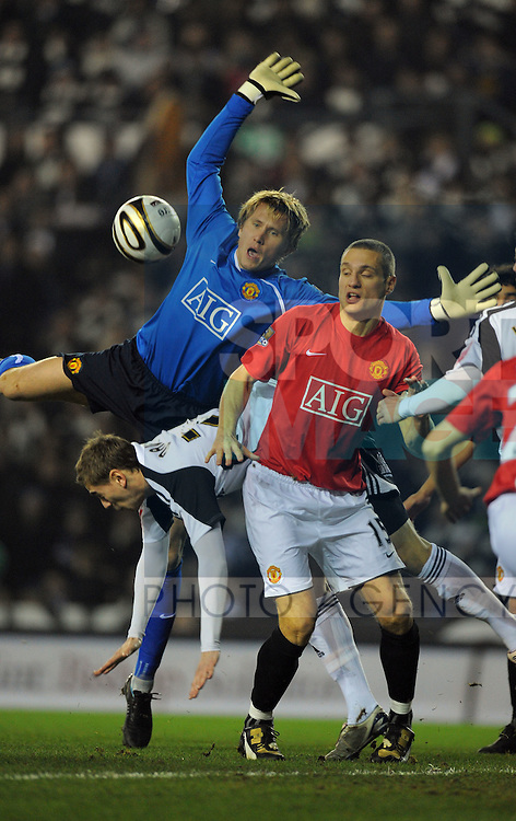 Manchester United's Tomasz Kuszczak and Nemanja Vidic of Manchester United flap at a cross under pressure from Steve Davies of Derby