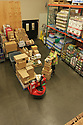 Warehouse worker with forklift and pallets of beverages