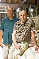 The owner and manager Cobroslav Barbaric sitting on an oak barrel, with Daniel Lay, in the winery. Hercegovina Produkt winery, Citluk, near Mostar. Federation Bosne i Hercegovine. Bosnia Herzegovina, Europe.