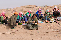 Chinese afforestation workers eat watermelons and bread for lunch in the desert areas of Minqin county in Gansu province, October 2016. Locals poke straw partway into the sand, forming a pattern of small squares. The grid like network of straw fences break the force of the wind at ground level, stopping dune movement by confining the sand within the squares of the grid. Minqin county is located in between the Tengger Desert and the Badain Jaran Desert.