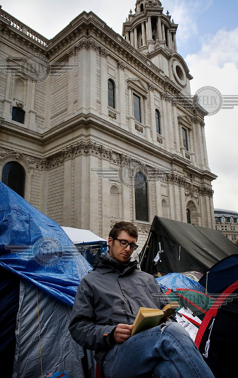 A man reads a book in the Occupy London protestor camp outside St Paul's Cathedral in the City of London. The protest is part of a worldwide movement against the banking industry and the prevailing economic system..