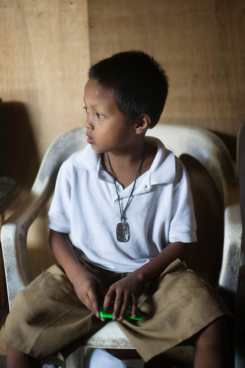 A boy sits in his home in a squatter village in Manila, Philippines.