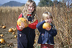 TWO SISTERS SELECT PUMPKINS FROM PUMKIN PATCH. THE TWO SISTERS  PROUDLY HOLD THEIR PUMPKINS.