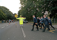 Lollipop lady on duty at school crossing patrol. She has stopped traffic to allow the schoolchildren to cross the road in safety. This image may only be used to portray the subject in a positive manner..©shoutpictures.com..john@shoutpictures.com