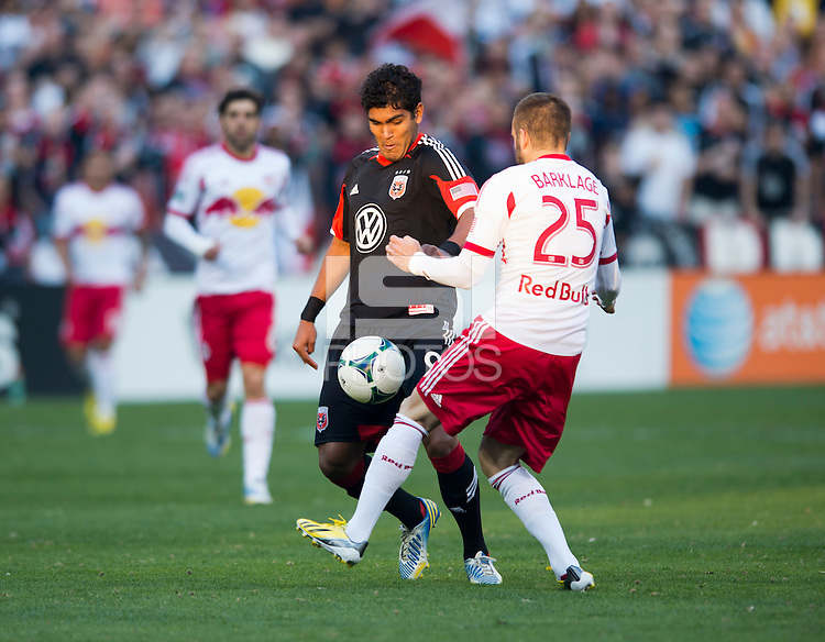 Rafael Teixeira (9) of D.C. United has the ball tackled away from him by Brandon Barklage (25) of New York Red Bulls during the game at RFK Stadium in Washington, DC.  New York Red Bulls defeated D.C. United, 2-0.