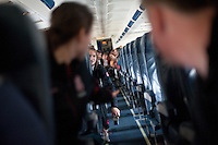 SAN JOSE, CA--Sara James passes a roll of duct tape to the front rows for a band tradition of rolling an object down the center aisle during takeoff at Atlantic Aviation en route to Norfolk, VA for the first and second rounds of the 2012 NCAA tournament.