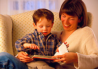 Mother reading a book to her young son while he sits on her lap.