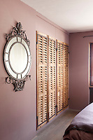 Window shutters have been restored and recycled as doors for this built in wardrobe in the bedroom