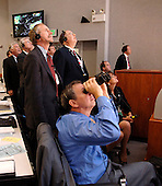 "In Firing Room 4 of the Launch Control Center, NASA Administrator, Dr. Michael Griffin (foreground) and other mission mangers watch the launch of Space Shuttle Discovery on mission STS-121.  Liftoff was on-time at 2:38 p.m. EDT.  During the 12-day mission, the STS-121 crew of seven will test new equipment and procedures to improve shuttle safety, as well as deliver supplies and make repairs to the International Space Station. Landing is scheduled for July 17 at Kennedy's Shuttle Landing Facility. Photo Credit: ""NASA/Bill Ingalls"""